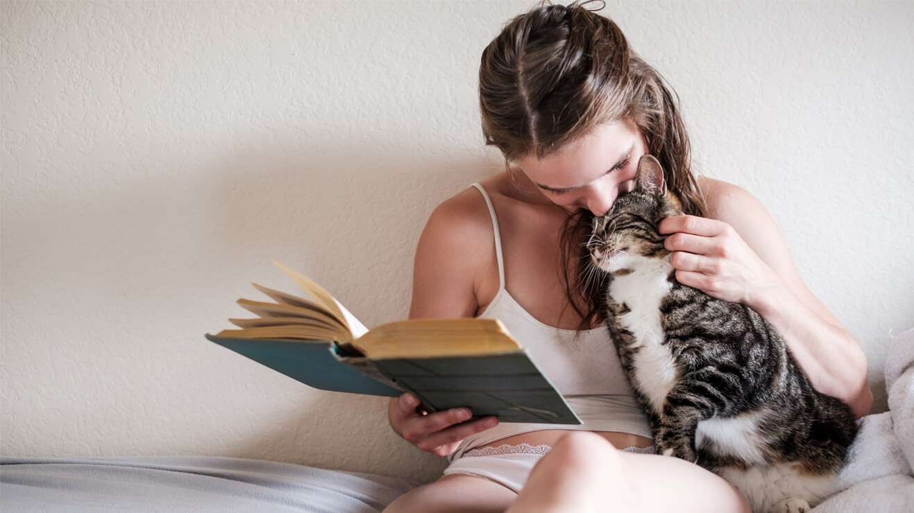 Lady reading with cat.